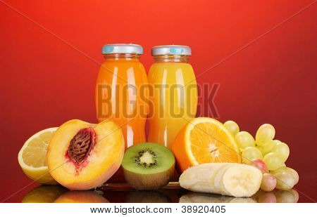 Delicious multifruit juice in a bottle and fruit next to it on red background