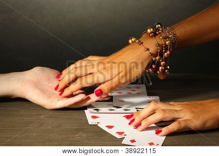 reading the lines hand and woman's hands on grey backcground