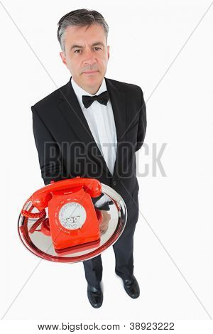 Waiter holding a red dial phone on a silver tray