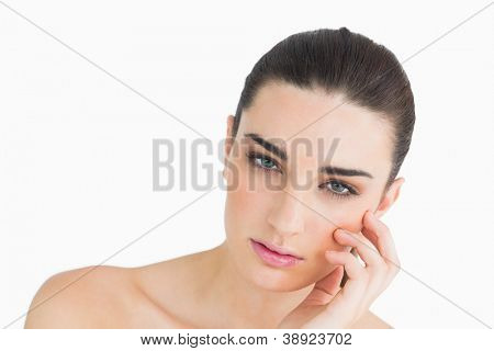 Pálida mulher olha tocar seu rosto, enquanto olhando para a câmera