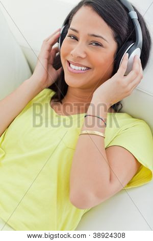 Portrait of a smiling Latino listening music on a smartphone while lying on a sofa
