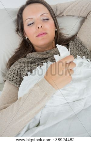 Sleeping woman lying on sofa with a cold in the living room