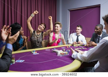 People cheering at poker table