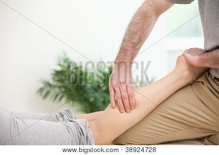 Physiotherapist pressing a leg with his fingers in a room