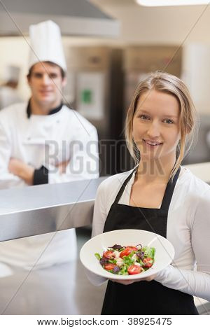 Waitress smiling and holding a salad in the kitchen