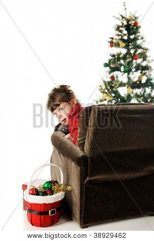 An adorable preschooler in her pajamas looking back from her overstuffed chair.  A Christmas tree is in the background and a basket of decorations sits by her side.  On a white background.
