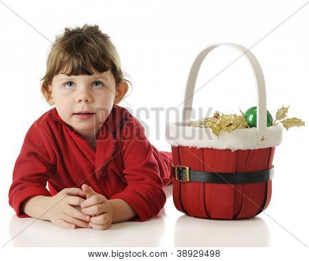 An adorable little girl in her red pajamas laying on the floor looking up by a basket of Christmas goodies.  On a white background.