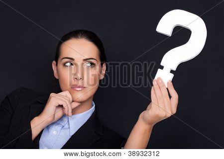 Beautiful businesswoman with a thoughtful expression holding a white question mark in her hand against a black studio background