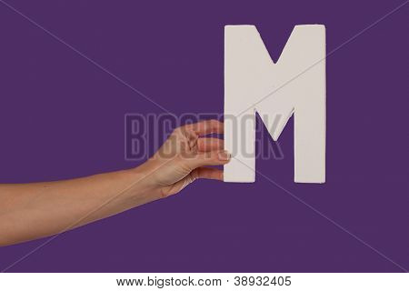 Female hand holding up the uppercase capital letter M isolated against a purple background conceptual of the alphabet, writing, literature and typeface