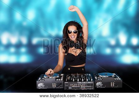 Jubilant sexy female disc jockey standing behind her mixing deck laughing and holding up her hand against a backdrop of blue party lights with copyspace