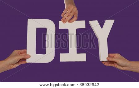 White alphabet lettering spelling DIY held up over a purple studio background by outstreched female hands