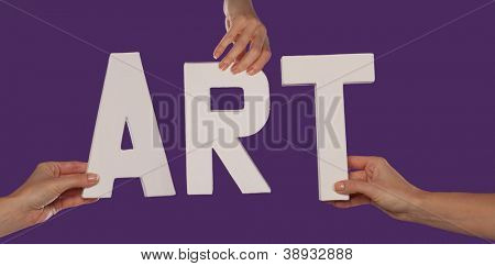 White alphabet lettering spelling ART held up over a purple studio background by outstreched female hands