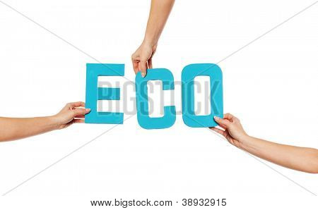 Turquoise blue alphabet lettering spelling ECO held up over an isolated white background by outstretched female hands