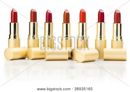 row of red lipsticks with refelction on white