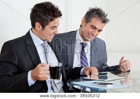 Two happy businessmen using digital tablet at desk in office