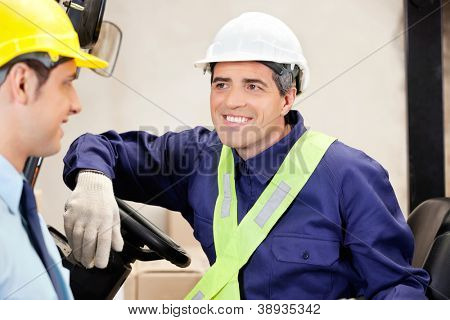 Happy forklift driver looking at male supervisor