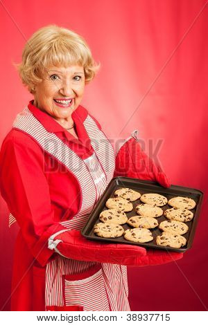 Sweet homemaker grandma holding a tray of fresh baked chocolate chip cookies.  Photographed in front of red background.