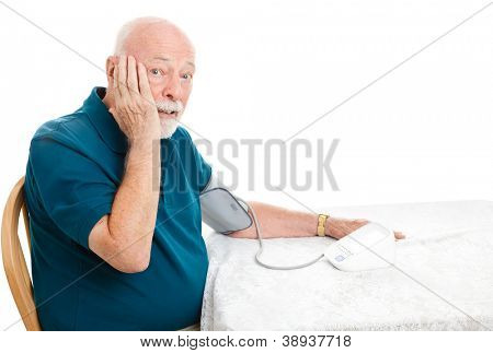Senior man taking his blood pressure and shocked by the results.  White background.