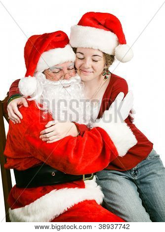 Adolescent girl sitting on Santa Claus' Lap, getting a hug.  We're never too old for Christmas!  White background.