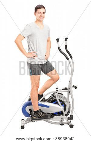 Full length portrait of an athlete standing on a cross trainer machine isolated on white background