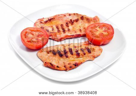 a plate with some slices of barbecued spiced chicken meat and raw tomato on white background