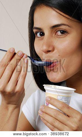 Young female enjoying and eating yogurt.