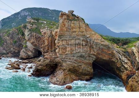 sea cave and rocks on coastline of beach of sea