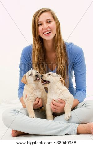 Puppies and happy teenage girl - portrait of young girl playing with labrador puppies