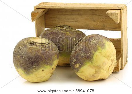 fresh turnip(brassica rape rapa) in a wooden crate on a white background