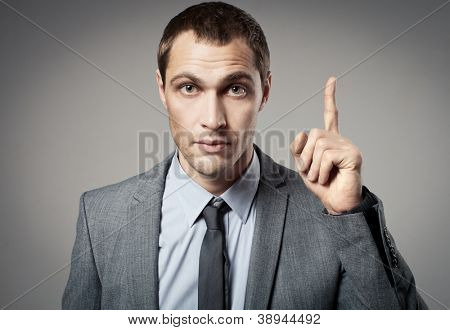 Young businessman criticizing on gray background