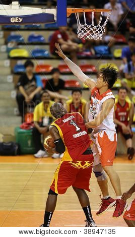 KUALA LUMPUR - OCTOBER 27: Farmcochem's Christopher Garnet #1 fakes a shot, defended by Dragons' John Ng in a Malaysia National Basketball League match on October 27, 2012 in Kuala Lumpur, Malaysia.
