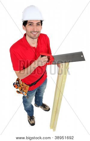 A carpenter sawing wood.
