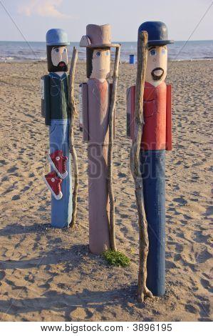 Three Wood Figures On Beach