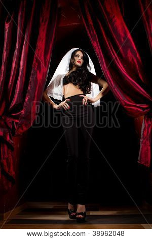 Halloween concept: sexy lady vampire over red curtain