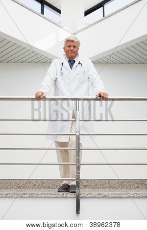 Smiling doctor in labcoat leaning against rail in hospital corridor