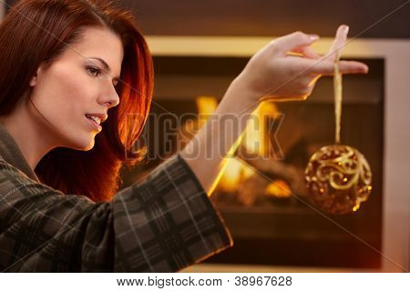 Woman holding fancy bulb christmas decoration on finger, in front of fireplace.