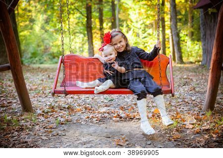 little beautiful sisters in autumn park