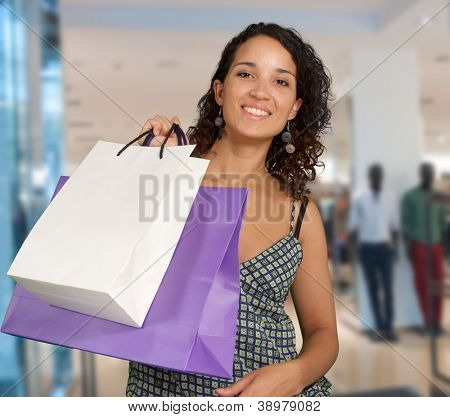 Happy exotic woman shopping at the mall