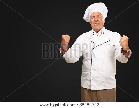 Portrait Of Angry Chef On Black Background