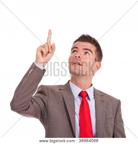 young business man pointing and looking up, on white background