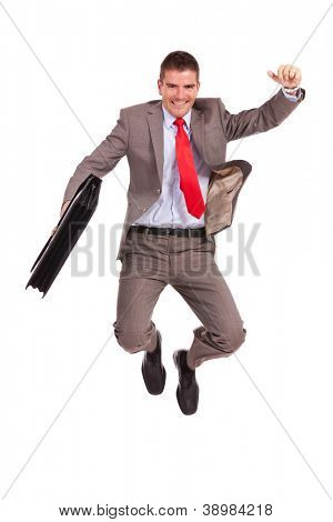 very happy young business man holding a briefcase and jumping of joy on white background