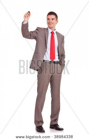 full body picture of a business man writing with marker and holding a hand in his pocket isolated on white background