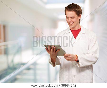 Retrato de joven académico sosteniendo una tableta digital a la entrada del edificio moderno