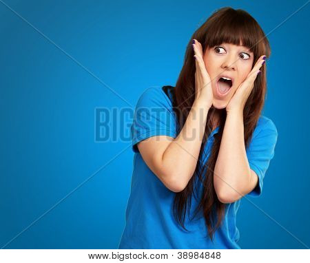portrait of surprised woman isolated on blue background