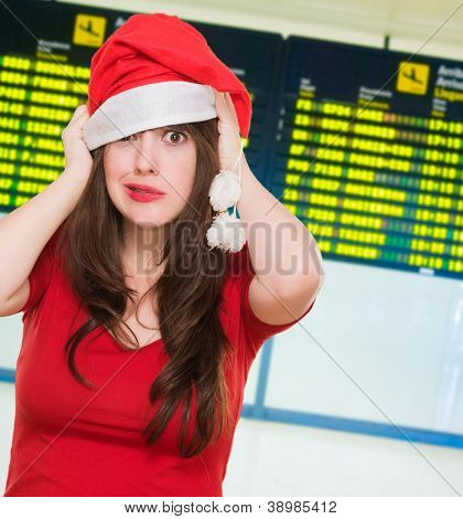 worried woman wearing a christmas hat at the airport