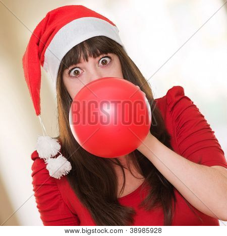 woman blowing balloon and wearing a christmas hat against an abstract background