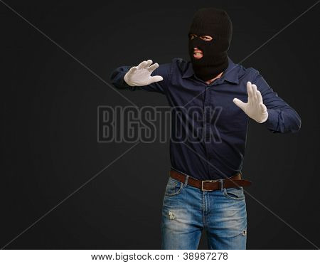 Burglar In Face Mask Isolated On Black Background