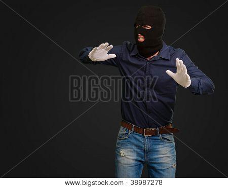 Burglar In Face Mask Isolated On Black Background