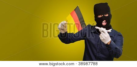 Man wearing a robber mask and holding airplane miniature and flag on yellow background