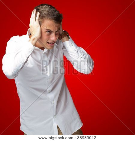 Portrait Of Young Man Covering His Ears With Hand On Red Background